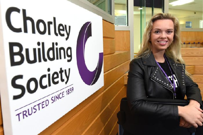 Staff member next to Chorley logo